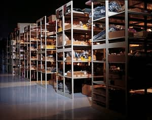 Dimly lit warehouse with shelves full of parts