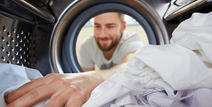 Background image of man grabbing clothes out of washing machine linking to contact us page.