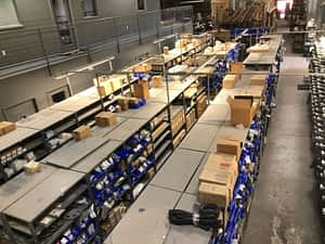 A view of a parts warehouse from the second floor showing rows of shelving with parts on them.