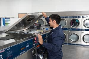 Dexter Service Technician opening top of washer during maintenance