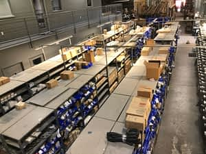 A view of the parts warehouse from overhead showing rows of shelving with parts on them.