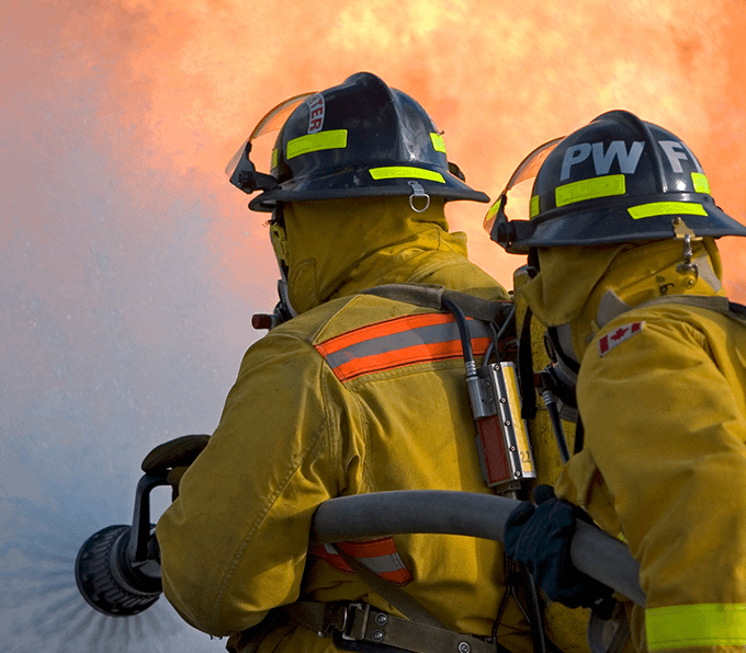 Background image of firefighters spraying a hose on a fire linking to PPE equipment